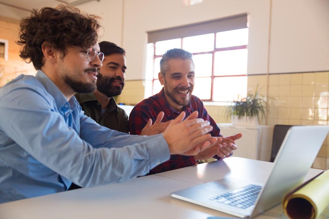 Group of coworkers watching online training or webinar